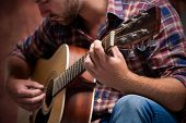 stock photo of guitar  - close up of a male musician playing acoustic guitar - JPG