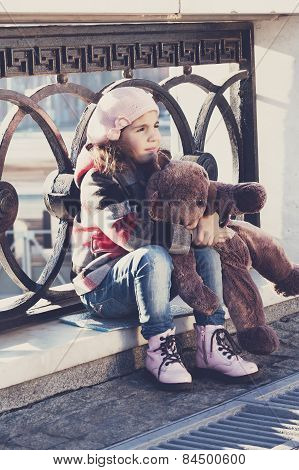 Little Girl In A Pink Beret Sits At A Fencing And Holds A Toy Bear In Hand
