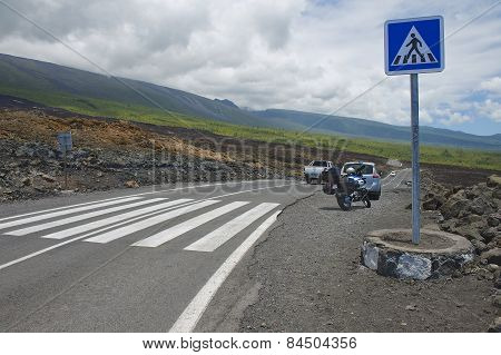 Pedestrian crossing of the asphalt road over volcanic lava in Sainte-Rose De La Reunion, France.