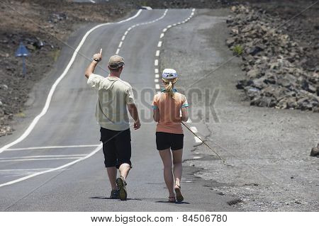 People walk by the asphalt road over volcanic lava in Sainte-Rose De La Reunion, France.