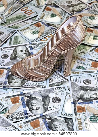 Women's Shoe On A Background Of Us Dollars Bills