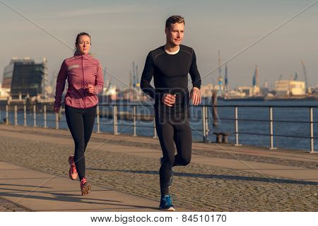 Young Couple Running On A Seafront Promenade