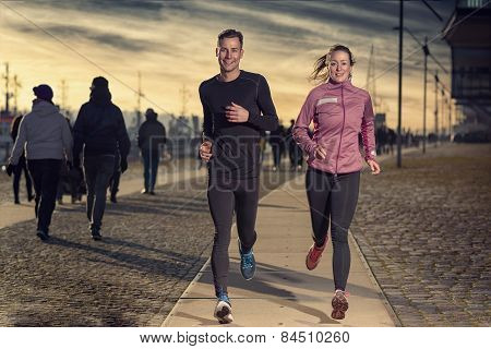 Active Young Couple Jogging On A Harbor Promenade
