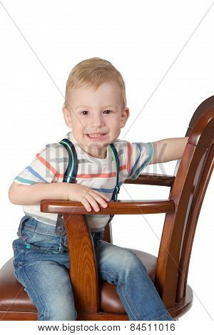 Portrait Of Little Boy Sitting In A Chair