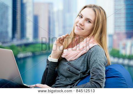 Young Girl Using Laptop In Comfy Armchair With Big City On The Background