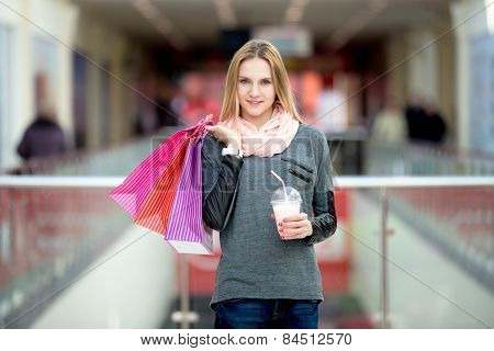 Smiling Young Woman Shopping, Holding Colorful Paper Bags And Milkshake