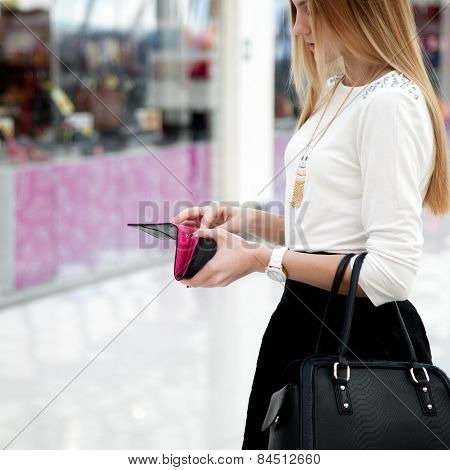 Young Female In Fashionable Clothes Looking Into A Wallet In Shopping Mall