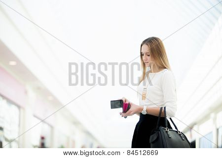 Young Female Standing With Opened Wallet In Shopping Mall