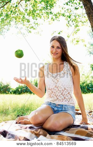 young girl throws up an apple. beautiful girl has a rest in the summer in the park.