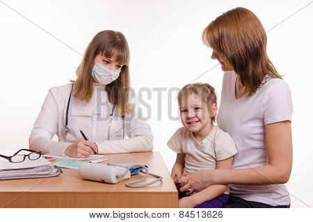 Young Mother With Her Child Sitting In His Office At The Pediatrician