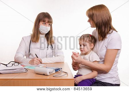 Pediatrician Talking In Office With A Young Mother With Child On Her Lap