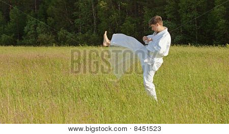 Man In Kimono Fulfills Blows By Feet In Field