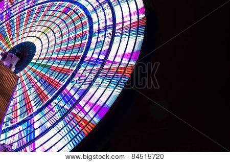 Bright Ferris Wheel Spinning Against Black Night Sky