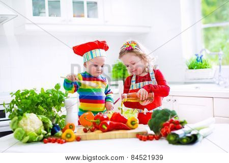 Kids Cooking Vegetables In A White Kitchen