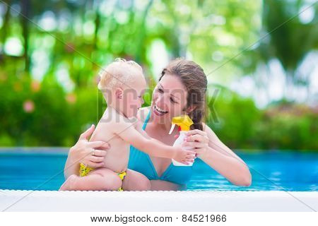 Mother Applying Sun Screen On Baby In Swimming Pool