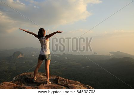 cheering woman open arms mountain peak