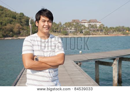 Portrait Of Asian Smart Man Standing And Smiling With Happy Face On Wood Piers Beside Blue Sea And B