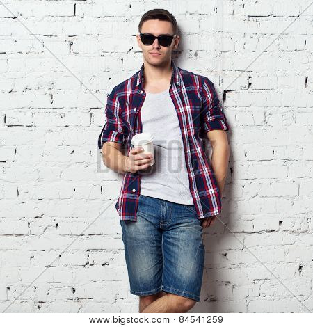 Handsome stylish young man jeans shorts shirt. Brutal bristle sunglasses  cofee brick wall