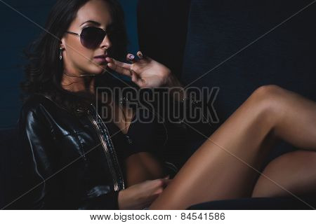 Sexy fashion brunette woman lying on blue armchair leather jacket and denim jeans shorts