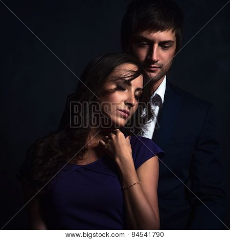 Curly brunette girl and handsome guy in a suit perfect romantic couple.