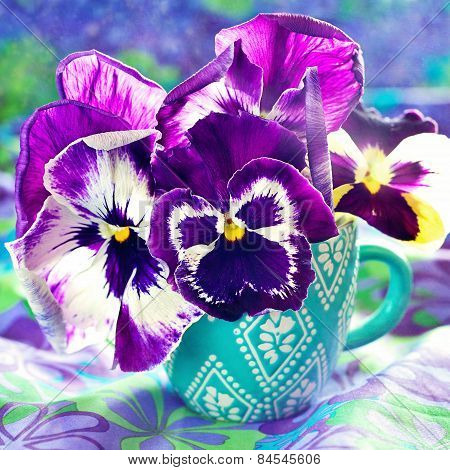 pansy flowers in a blue cup .