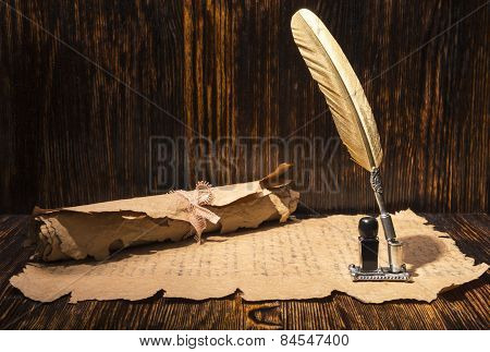 Vintage golden pen and ancient manuscripts on a wooden background