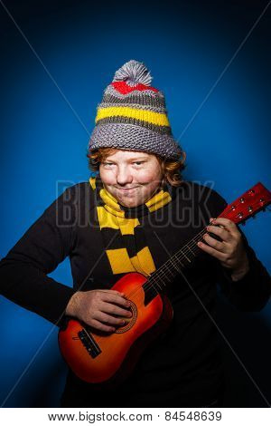 Red-haired Expressive Teenage Boy Playing On Ukalele