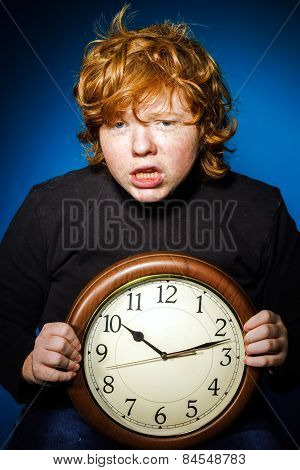 Expressive Red-haired Teenage Boy Showing Time On Big Clock