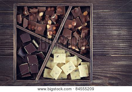 Rustic Wood Box With Set Of Chocolates  On Dark Wooden Table