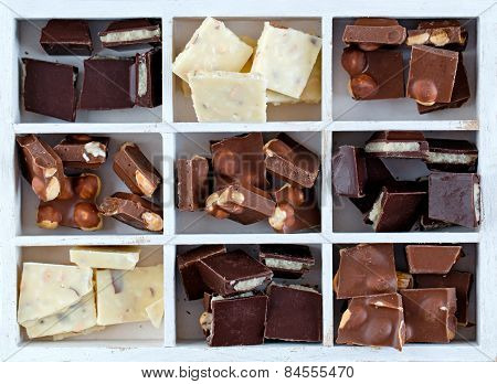 White Box With Set Of Chocolates On Wooden Table Isolated
