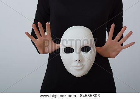 white theatrical mask in her hands.on white background