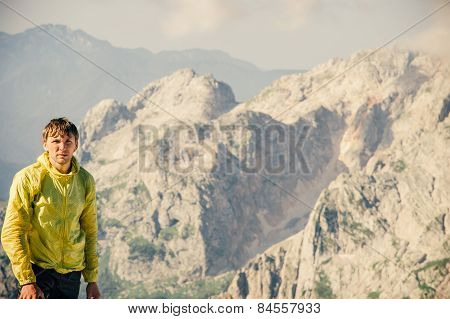 Man Traveler hiking in Mountains with beautiful summer landscape on background