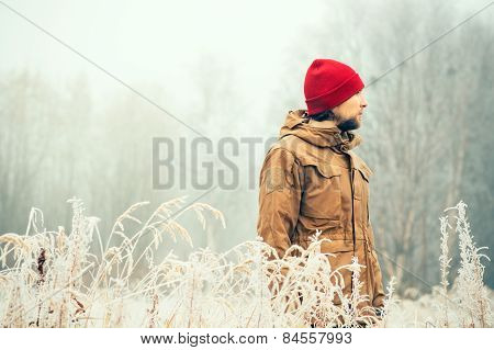 Young Man wearing winter hat clothing outdoor with foggy forest nature on background Travel Lifestyl