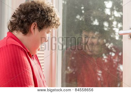 Mentally Disabled Woman Looking To Her Reflection At The Window