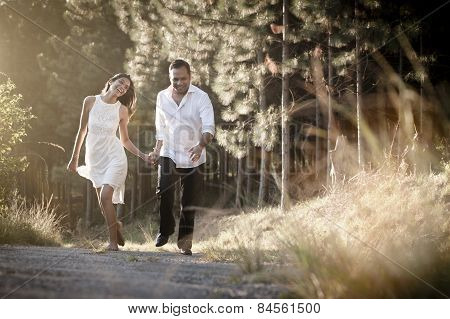 happy flirtatious Indian couple walking along dirt road together