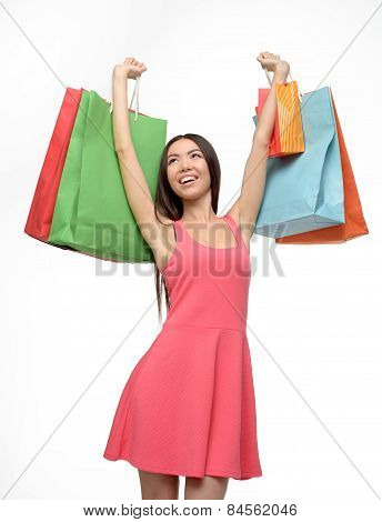 Asian woman after shopping with hands up and bags
