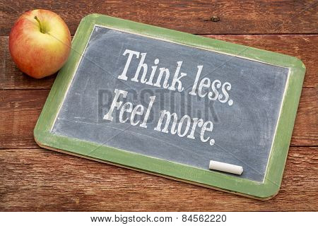 Think less. Feel more.  Motivational words on a slate blackboard against red barn wood