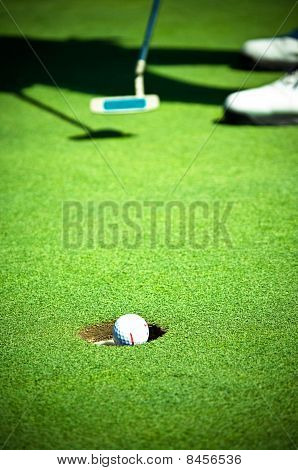 Golf ball entering the hole