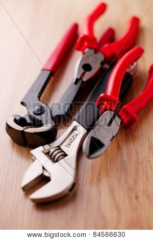 Adjustable Wrench, Pliers, Claw Hammer And Pliers On The Wooden Background
