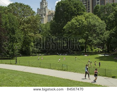 People Jogging And Children Playing In Central Park