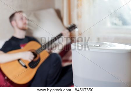 Man Playing Guitar On The Background Of Humidifier
