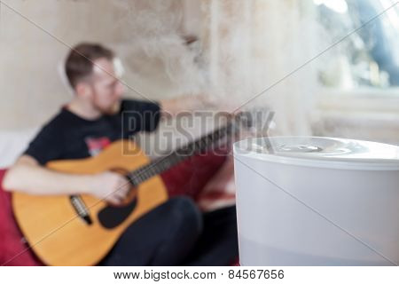 Man Tuning His Guitar On The Background Of Humidifier