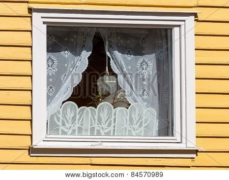 window in a wooden house with white curtains