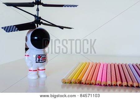 Child's Toy Spaceman Looking Towards A Set Of Colorful Pencil Crayons On White Background.