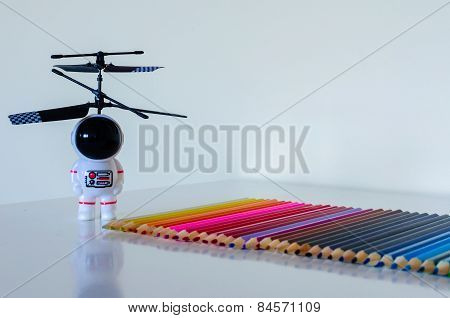 Head-on Child's Toy Spaceman Looking Towards A Set Of Colorful Pencil Crayons On White Background