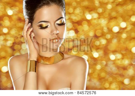 Makeup. Jewelry. Glam Lady. Beauty Fashion Girl Model Isolated Over Sparkling Golden Background.