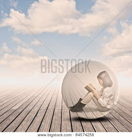 little girl reading a book inside a bubble on a wharf