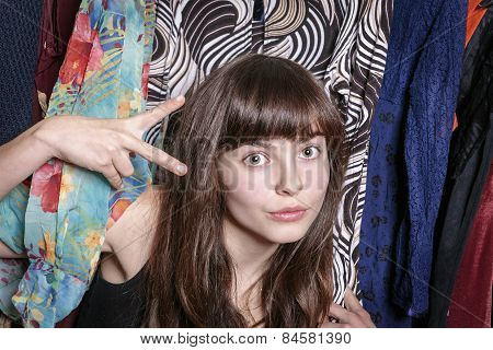 Teenage Girl With Her Wardrobe Showing  A Scissors With One Hand
