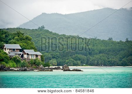 View Of Seychelles Coastline With A House In The Forest