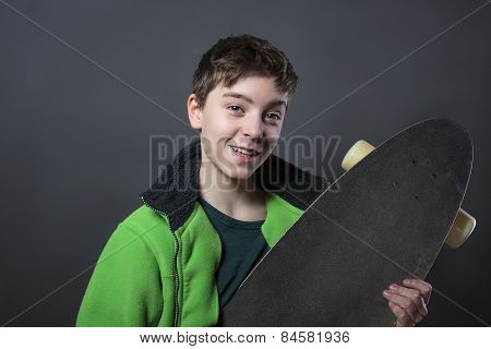 Proud Smiling Teenage Boy Holding His Long Board, With Gray Background